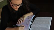 woman journaling and an open Bible