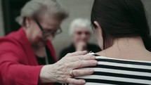 group of elderly women praying over a young woman