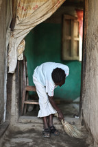 woman sweeping the dirt floor of her house in Ethiopia