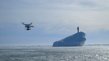 Man Standing On Iceberg with drone filming