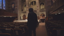 hooded man walking into an empty church