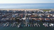Aerial view of large beautiful boat harbor, houses, peninsula, and beach.