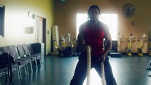 a man slamming ropes in the gym