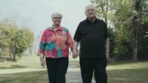 senior couple walking holding hands