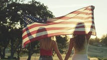 young woman walking with an American flag draped over their backs