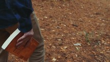 a man carrying a Bible walking into the woods