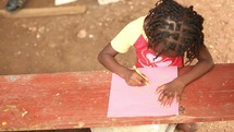 a child coloring in Haiti