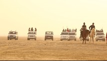 men in SUV's and on horses in the desert
