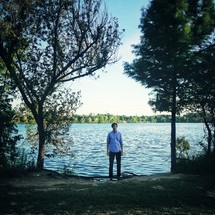 Man standing in front of a lake