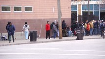 a line of people in front of a homeless shelter