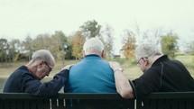 elderly men praying together sitting on a park bench