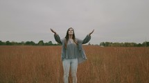 a woman with raised hands standing in a field