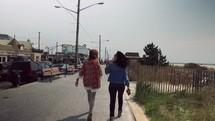 women walking down a sidewalk heading to a beach