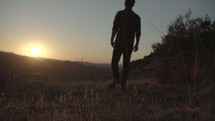 man walking into the sunset