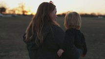 a woman carrying her toddler son outdoors at sunset