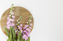 pink flowers on a circular wood board
