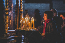 women lighting candles in a sanctuary