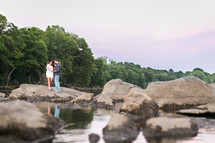 coupe standing on rocks on a shore holding hands
