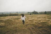 A woman runs through a meadow.