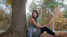 sad woman sitting under a tree
