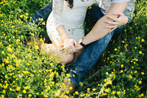 a couple sitting in a meadow of yellow flowers