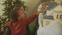 a child admiring a Christmas village display