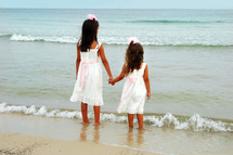 sisters holding hands on a beach