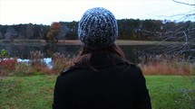 woman standing by a pond looking out at fall colors