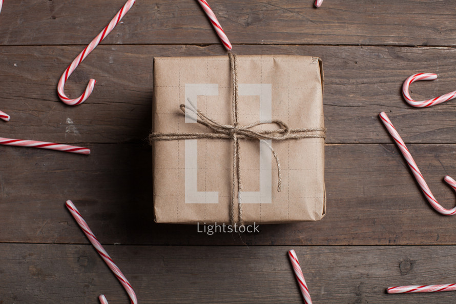 candy canes spread out on a wood floor and wrapped gift