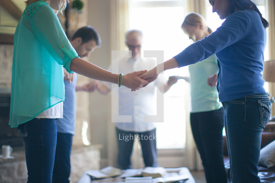 Group holding hands in prayer — Photo by Pearl - Lightstock