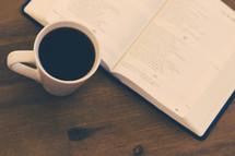 open Bible and coffee mug on a table