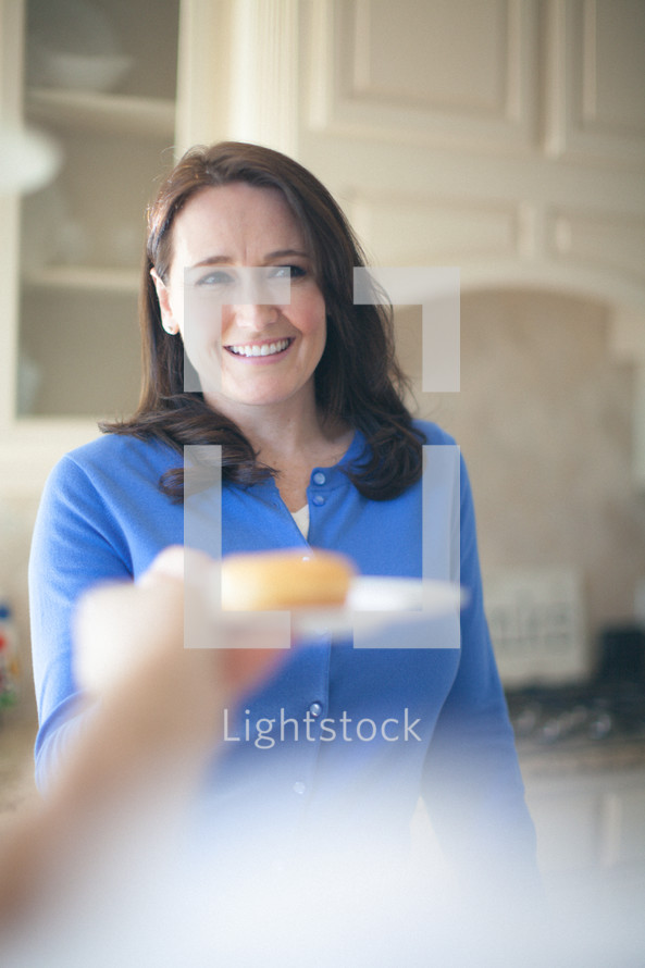 woman serving a donut on a plate