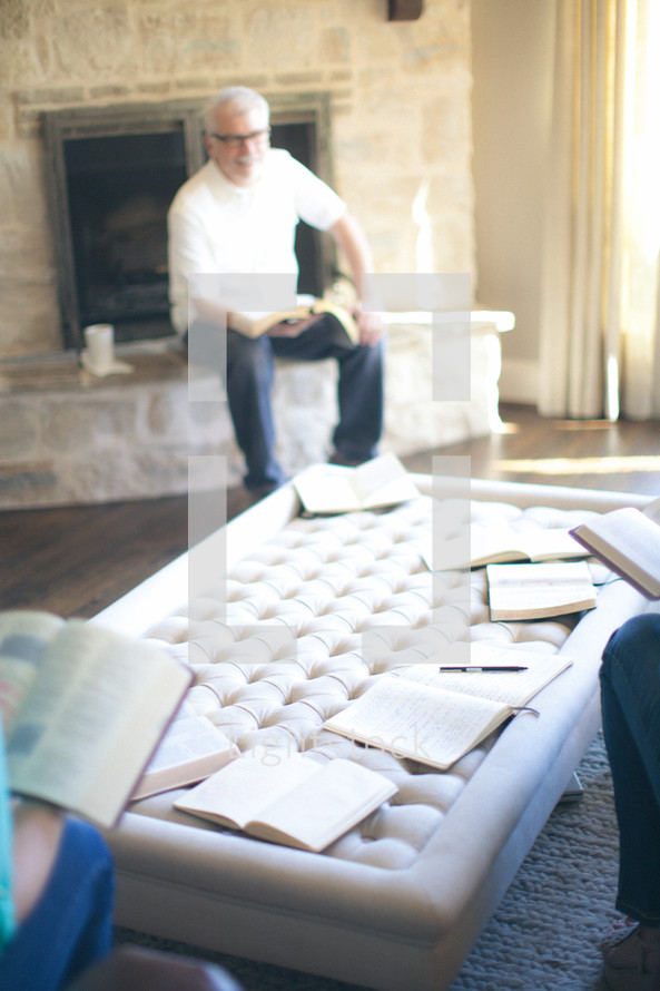 Man sitting on fireplace hearth during Bible study.