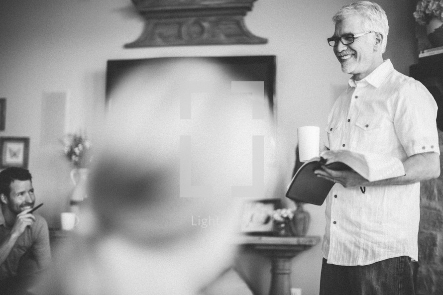 Smiling man holding a Bible at a Bible study.