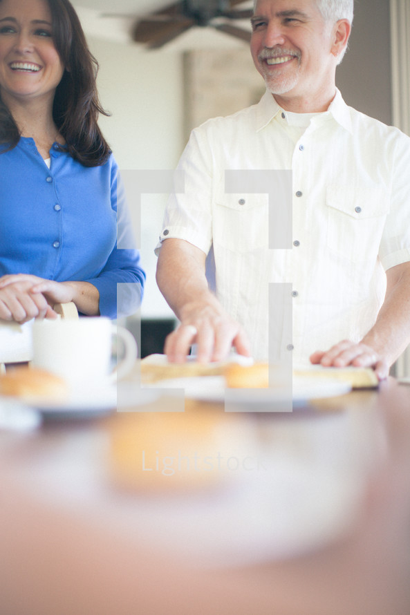 man and woman standing at a table next to coffee, donuts, and Bibles