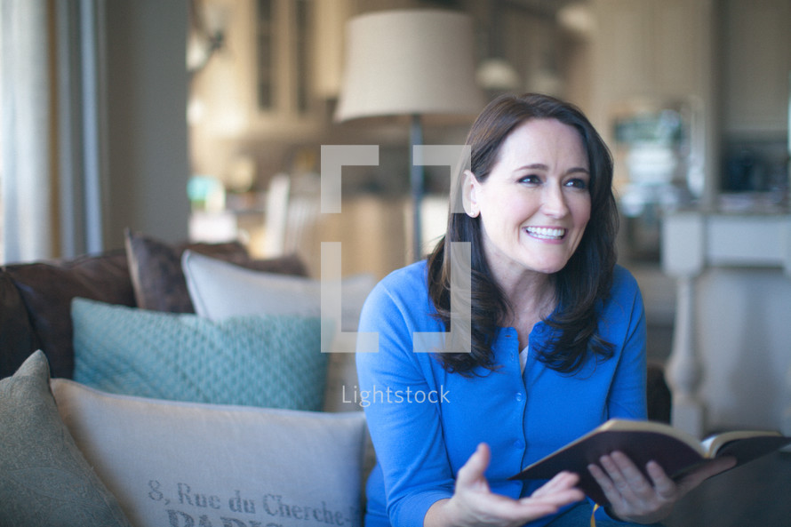 woman holding a bible and talking at a Bible study