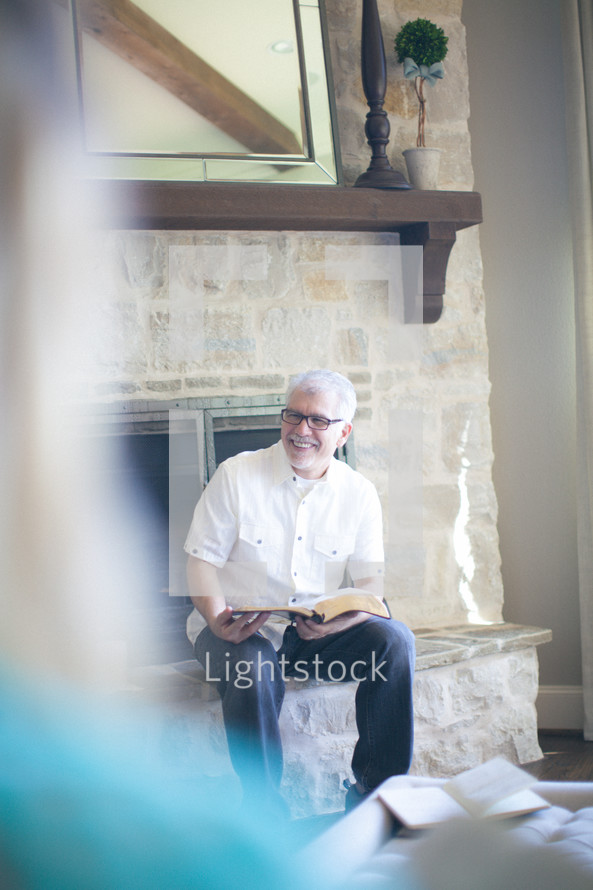 Smiling man sitting on a fireplace hearth during a Bible study.