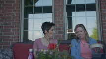 women sitting on a porch talking