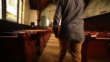 man walking into a church carrying a Bible