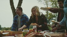 friends gathering food from a table at a cookout