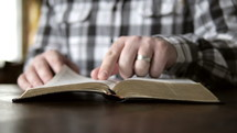man sitting, opening a Bible, and reading