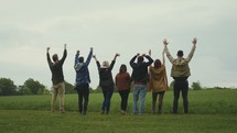 group standing together in a field with hands raised