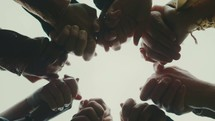 looking up into a group holding hands in prayer