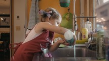 a toddler girl washing dishes
