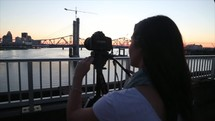 teen girl with a camera on a bridge