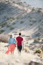 Couple walking across hills.