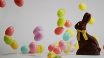 falling Easter eggs around a chocolate bunny on a white background