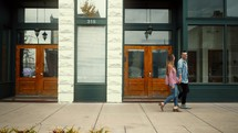 a couple walking down a sidewalk holding hands