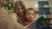 mother reading Christmas books to her children