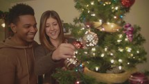 husband and wife decorating a Christmas tree